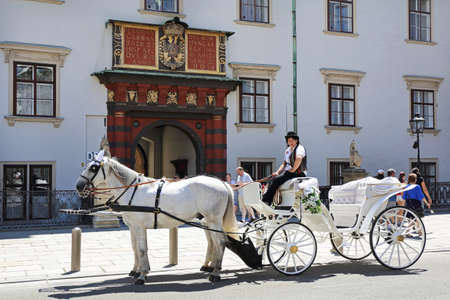 VIENNA, AUSTRIA - JULY 11, 2015: White Horse Drawn Carriage in Front of Hofburg Imperial Palace in Vienna, Austria.