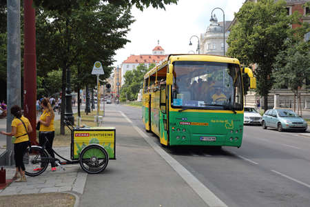 VIENNA, AUSTRIA - JULY 12, 2015: Two Promoters With Cargo Bicycle and Sightseeing Tourist Bus in Vienna, Austria. Redactioneel