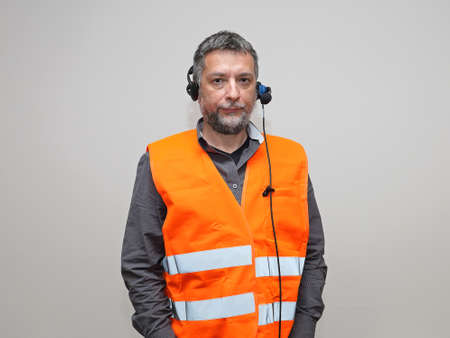 Senior Worker With Voice Control Headset and Safety Vest
