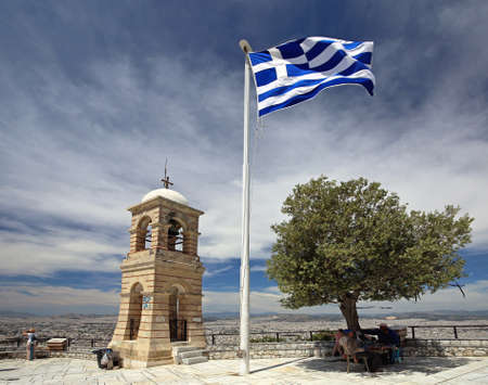ATHENS, GREECE - MAY 02, 2015: Greek Flag Olive Tree and Bell Tower at Top of Mount Lycabettus in Athens, Greece. Editorial