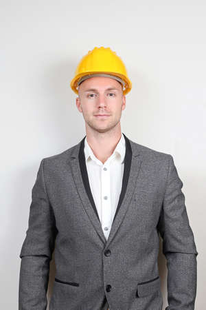 Young Businessman in Gray Suit with Yellow Hard Hat Banque d'images