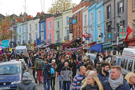 London, United Kingdom - November 23, 2013: Bunch of Tourists and Colorful Houses at Portobello Road Saturday in London, UK.