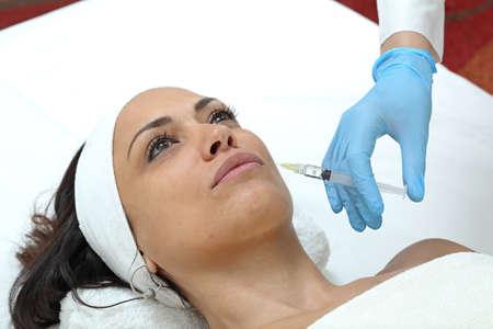 Woman Having Lips Augmentation Filler Injection at Beauty Clinic Фото со стока - 129827134
