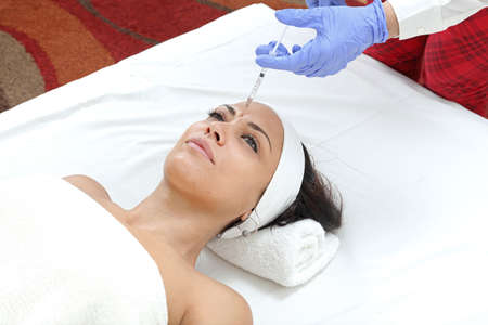 Woman Having Forehead Injection Filler Treatment at Beauty Clinic Фото со стока - 129827135