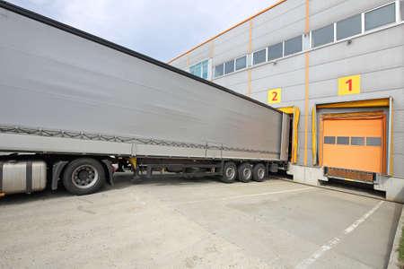 Vrachtwagenaanhangwagen laden bij de laaddeur van het magazijn