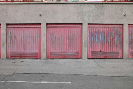 Several Closed Garage Doors With Faded Paint Stockfoto