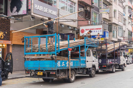 KOWLOON, HONG KONG - APRIL 21, 2017: Workers Unloading Trucks With Bamboo Scaffoldings at Construction Site at Mong Kok in Kowloon, Hong Kong. Editoriali
