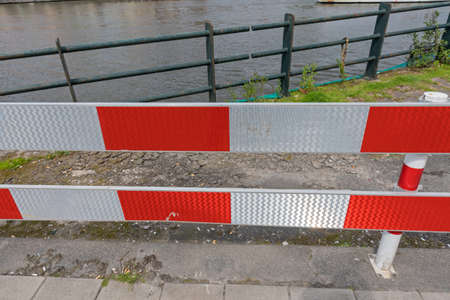 Red and White Reflective Barrier Near Canal Water Stock Photo
