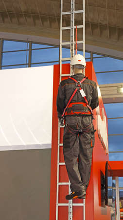 Worker on a Ladder With Safety Harness Protection