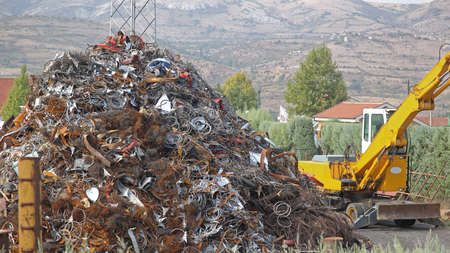 Pile of Scrap Metal and Digger at Recycling facility