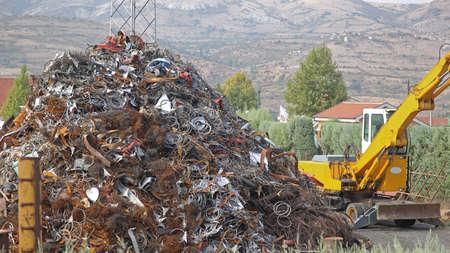 Pile of Scrap Metal and Digger at Recycling facility