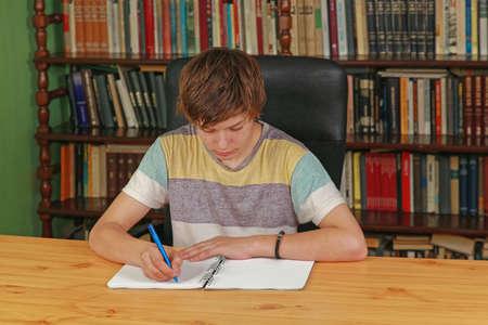 Teenage Boy Writing at Desk in School Library