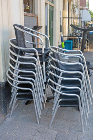 Stacked Metal Chairs in Front of Cafe Stock Photo
