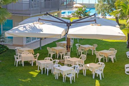 White Plastic Tables Under Parasol in Garden