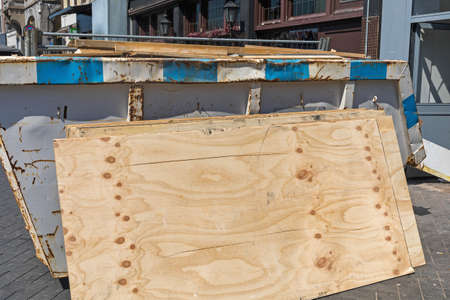 Plywood Boards and Skip Dumpster at Street