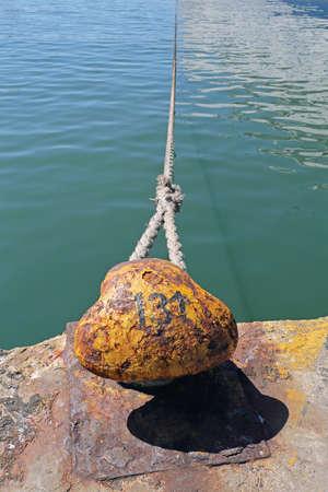Rusty Mooring Bollard With Long Rope in Port Standard-Bild