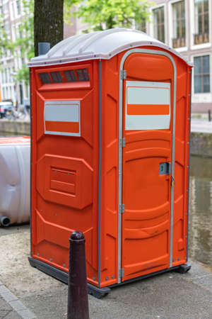 One Orange Portable Toilet Cabin at Canal