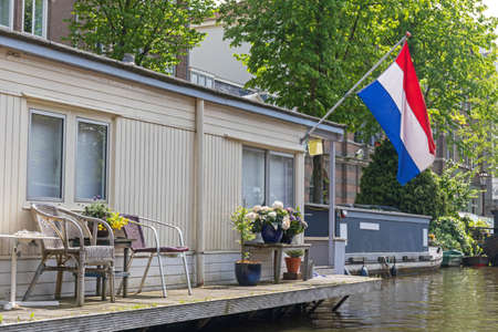 Houseboat With Holland Flag at Canal in Amsterdam
