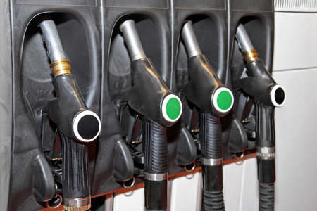 Four fuel nozzles handles at gas station