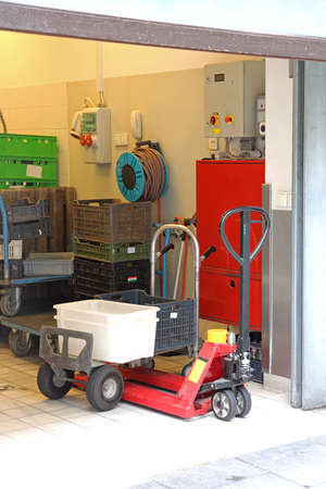 Pallet Jack and Dolly Cart With Crates in Storage Room