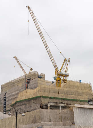 Crane and Bamboo Scaffoldings at Construction Site in Hong Kong
