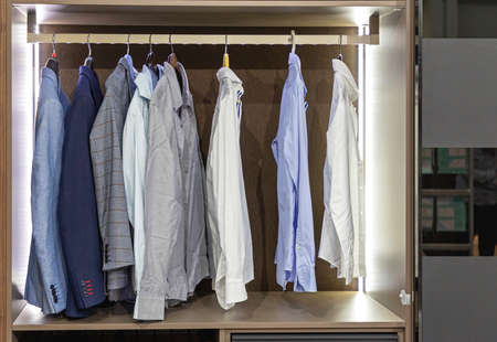 Business Shirts and Suits at Hangers in Wardrobe Closet