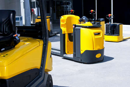 Yellow cargo pallet transporters and fork lifters