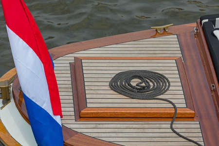 Rope Coil at Wooden Deck Boat With Flag