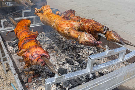 Roasting Pigs and Lambs Over Charcoal at Rotisserie Spit