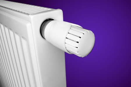 Radiator with thermostat valve isolated on violet gradient  photo