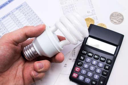 ahorro energia: Bombilla pizca calculadora y monedas