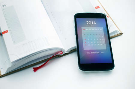 Modern mobile phone with calendar for February 2014  Concept for business devices photo