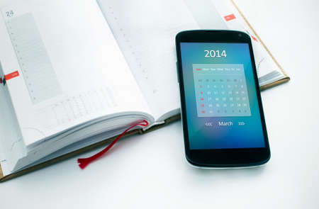 Modern mobile phone with calendar for March 2014  Concept for business devices photo
