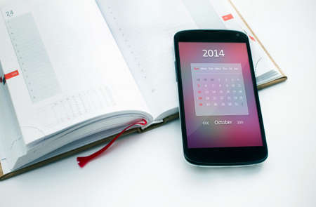 Modern mobile phone with calendar for October 2014  Concept for business devices photo