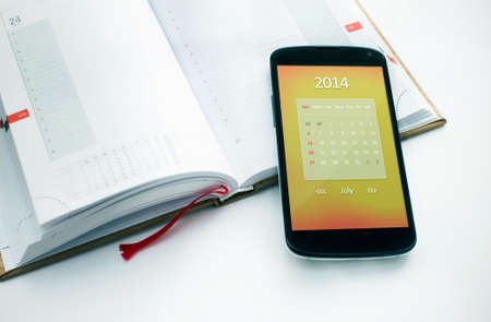 Modern mobile phone with calendar for July 2014  Concept for business devices photo