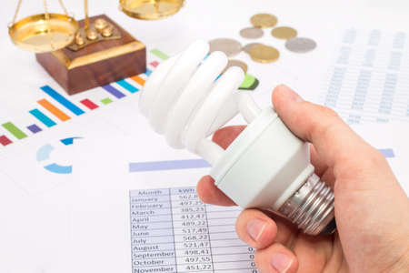 Light bulb whit graph and euro coins  The idea of ​​saving energy and money