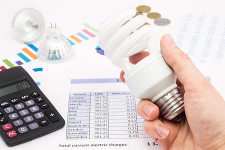 Light bulb whit calculator and euro coins  The idea of saving energy and money Stock Photo