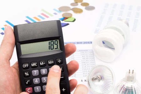 Light bulb, calculator and euro coins  The idea of ​​saving energy and money