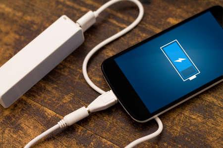 Telefoon opladen met energie bank. Scherptediepte op Power Bank Stockfoto