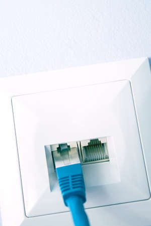 LAN cable plugged into the wall outlet Stock Photo
