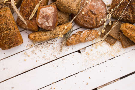 pumpkin seeds: Different types of bread on white wooden board Stock Photo