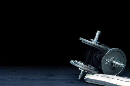 weight room: Composition with dumbbells and towel on wooden board