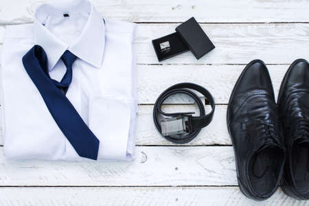 Man's style accessories. Composition on white wooden board