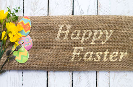 Colorful easter eggs on linen cloth with Happy Easter text photo