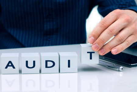 Businessman arranging small blocks with word Audit