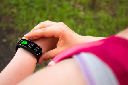 looking at watch: Sporty woman using smart watch. Interface on watch screen was generated in graphical program