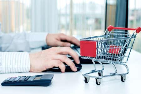 L'uomo alla scrivania con il suo computer portatile e un carrello in miniatura. Concezione di shopping su Internet Archivio Fotografico - 44054986