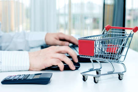supermarket checkout: Man at the desk with his laptop and a miniature trolley. Conception of shopping on the internet Stock Photo