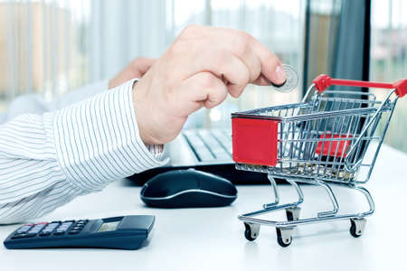 Man throws a coin into money box of the shape of trolley. Conception of shopping on the internet