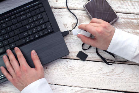 Man's hand puts pendrive into laptop. Concept of data storage.
